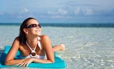 žena se slunečními brýlemi u moře